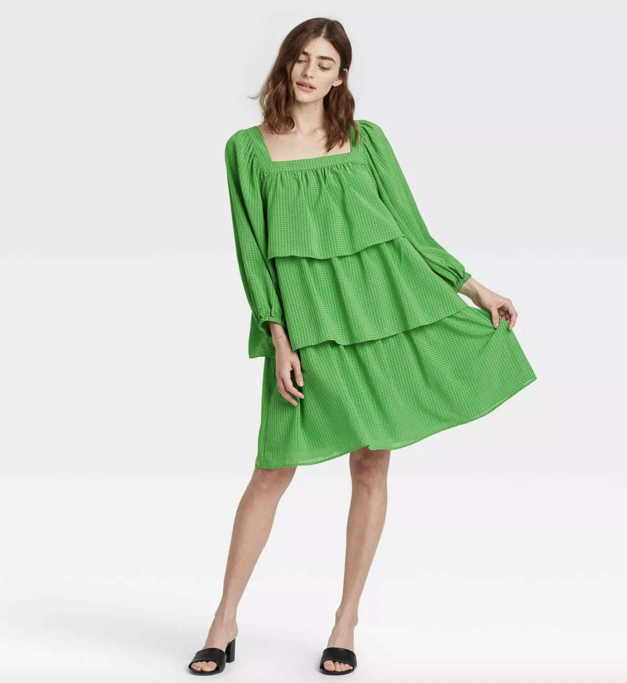 A woman wearing a green ruffle dress with black sandals