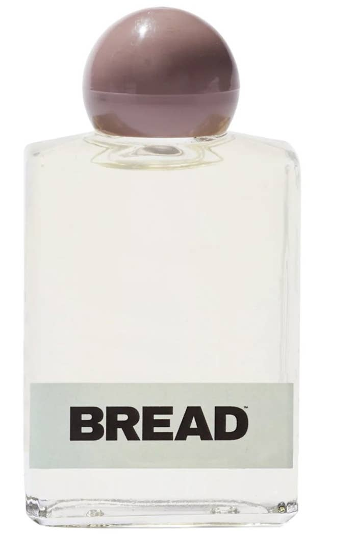 """The hair oil bottle says """"BREAD"""" with a light green stripe and taupe rounded lid"""