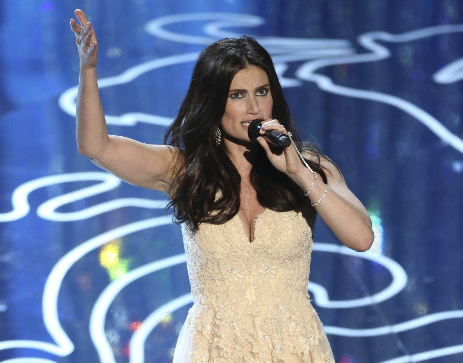 Idina throws her hands in the air while performing at the Oscars