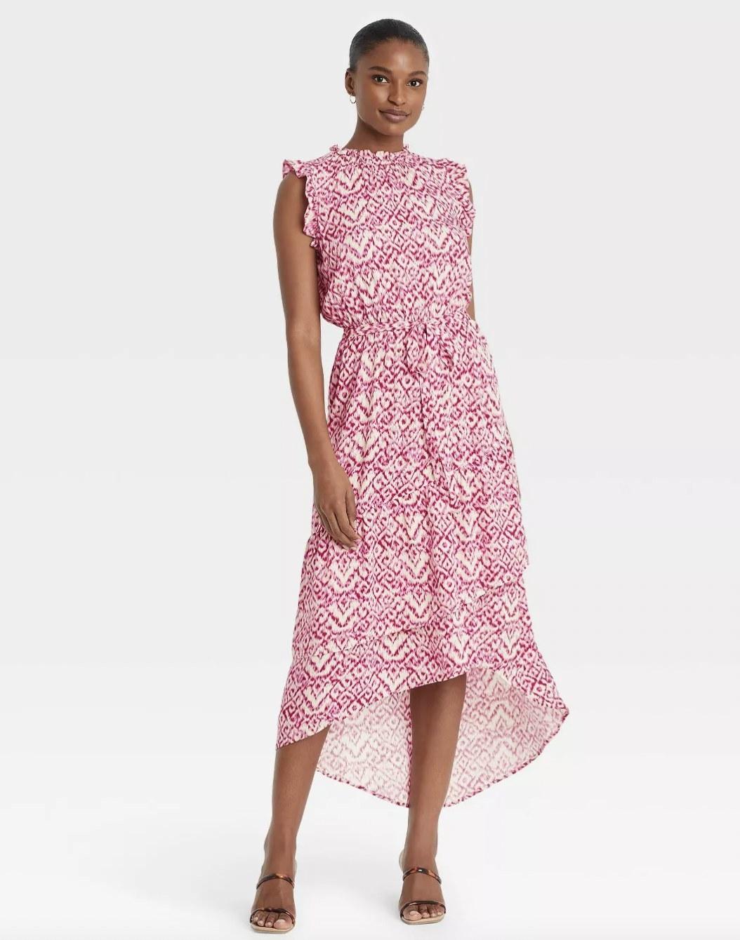A woman wearing a pink and white pattern dress
