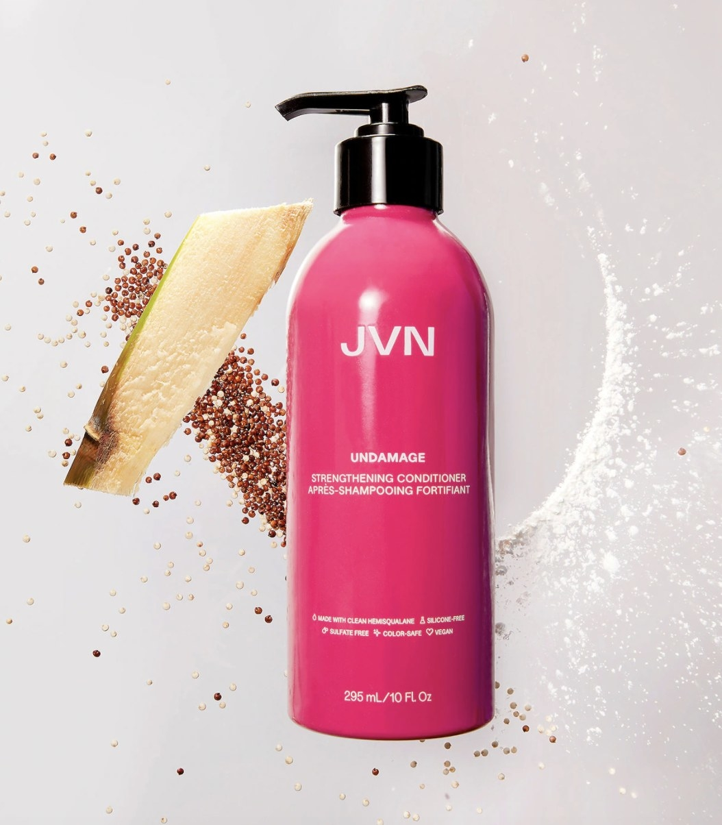 """The pink bottle with a black pump spout says """"JVN UNDAMAGE"""" and has has some of the items in the formula rested against the background behind the bottle"""
