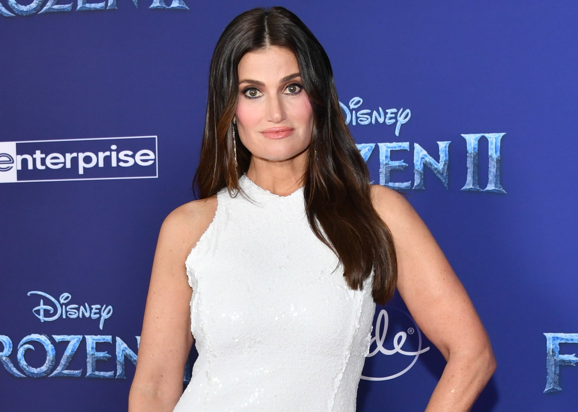 Idina poses in a white gown at a premiere