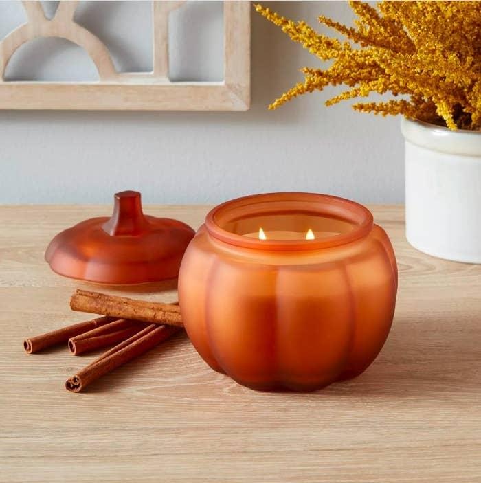 The medium sized orange pumpkin-shaped candle
