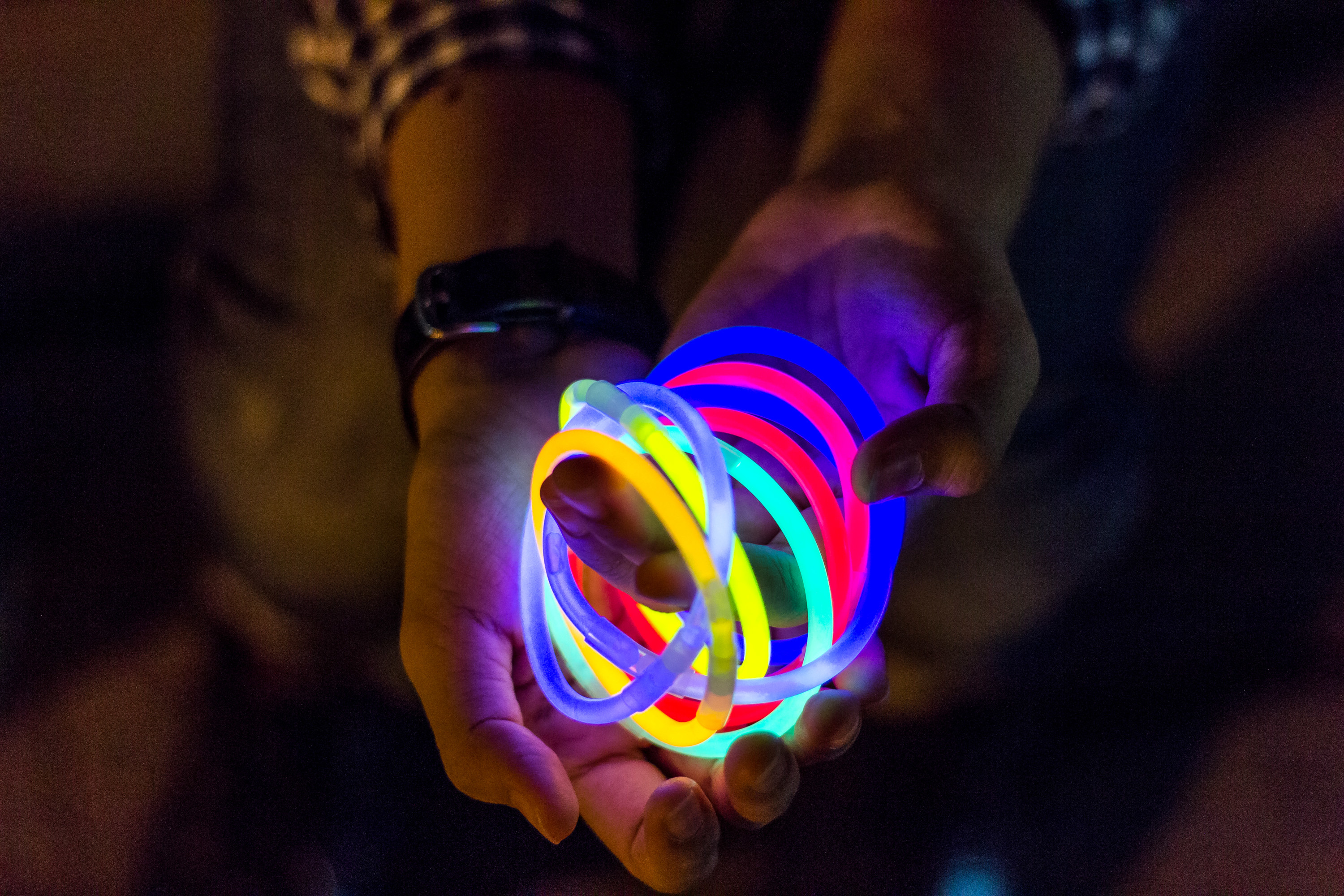An outstretched pair of hands holds several intertwined neon bracelets.
