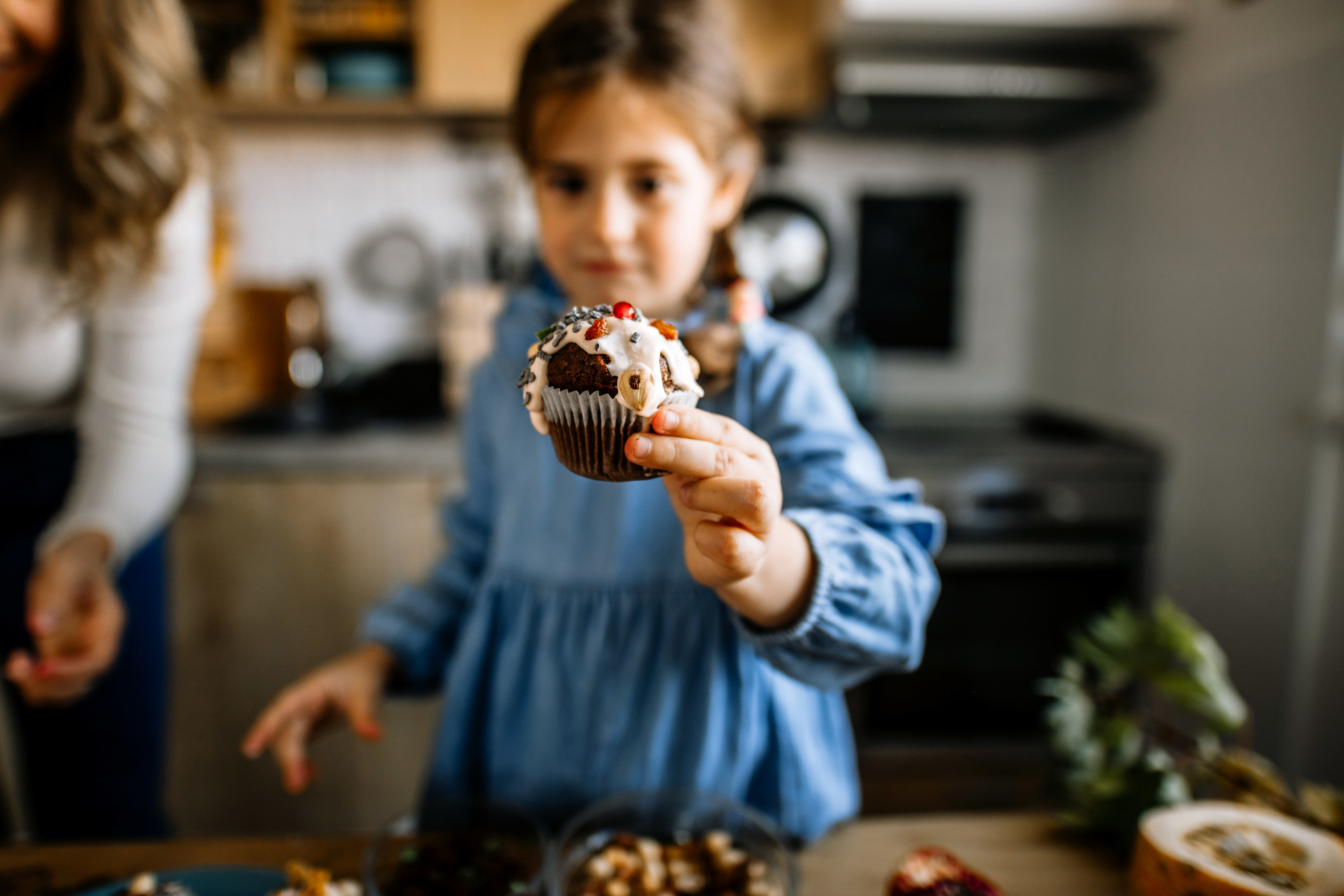 A little girl holds up a cupcake