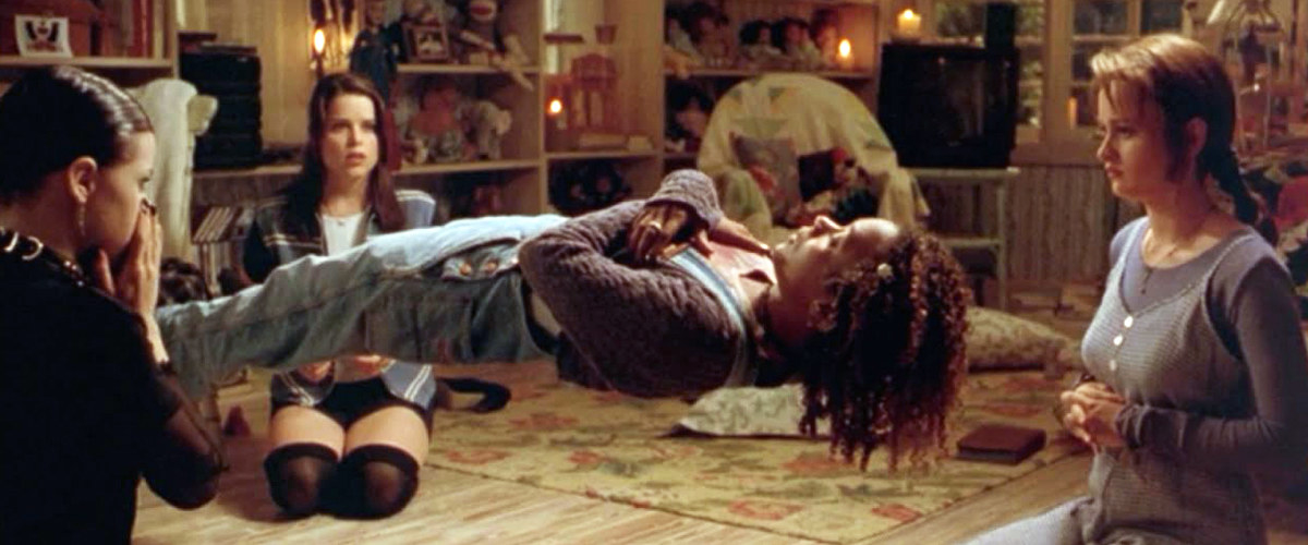 """A still from the movie, The Craft, in which girls succeed in levitating their friend by playing """"Light as a feather, stiff as a board"""""""