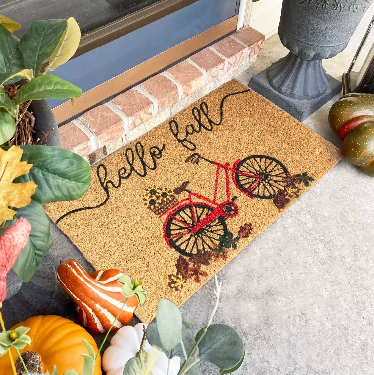 """The tan doormat with a bicycle design and the words """"hello fall"""" in cursive"""