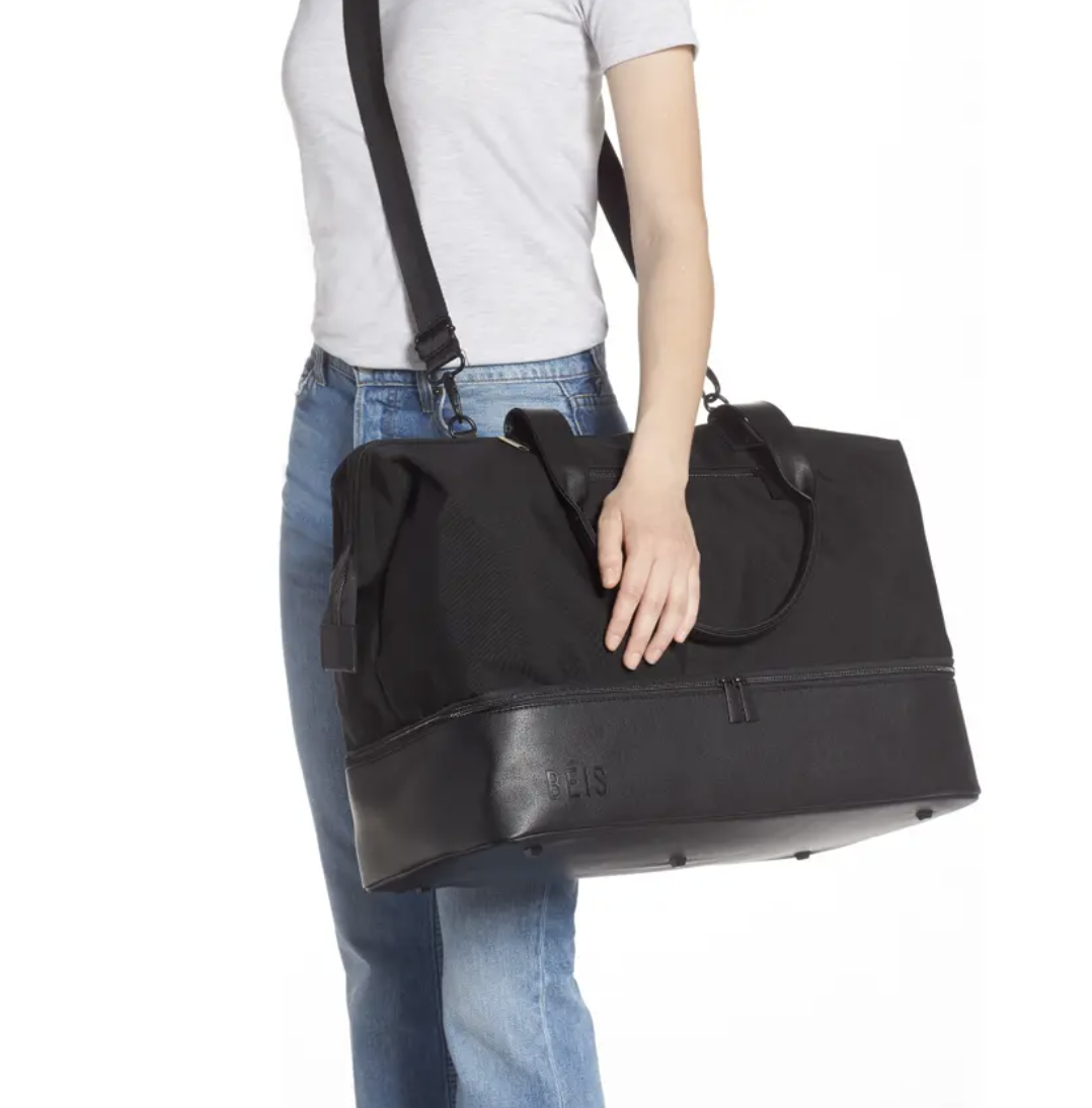 Model using the crossbody strap to hold a black zippered duffel bag with handles
