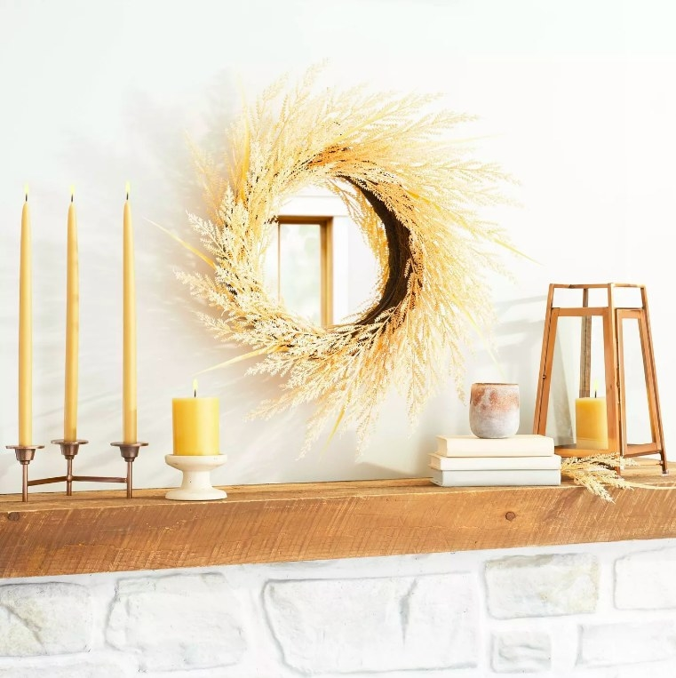 The gold wreath hung inside to frame a mirror above the mantlepiece