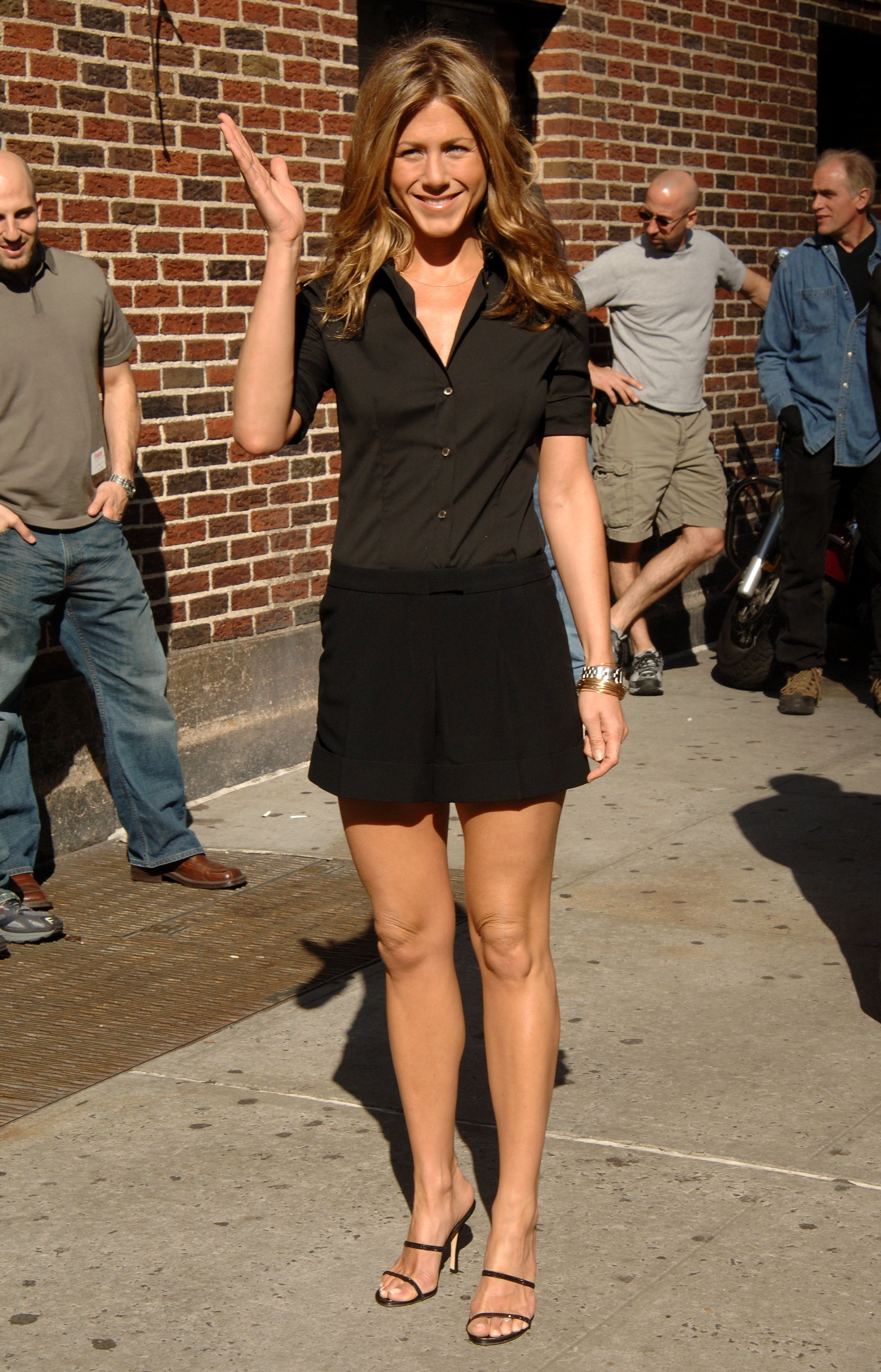 Jennifer waving to a crowd of fans and photographers outside