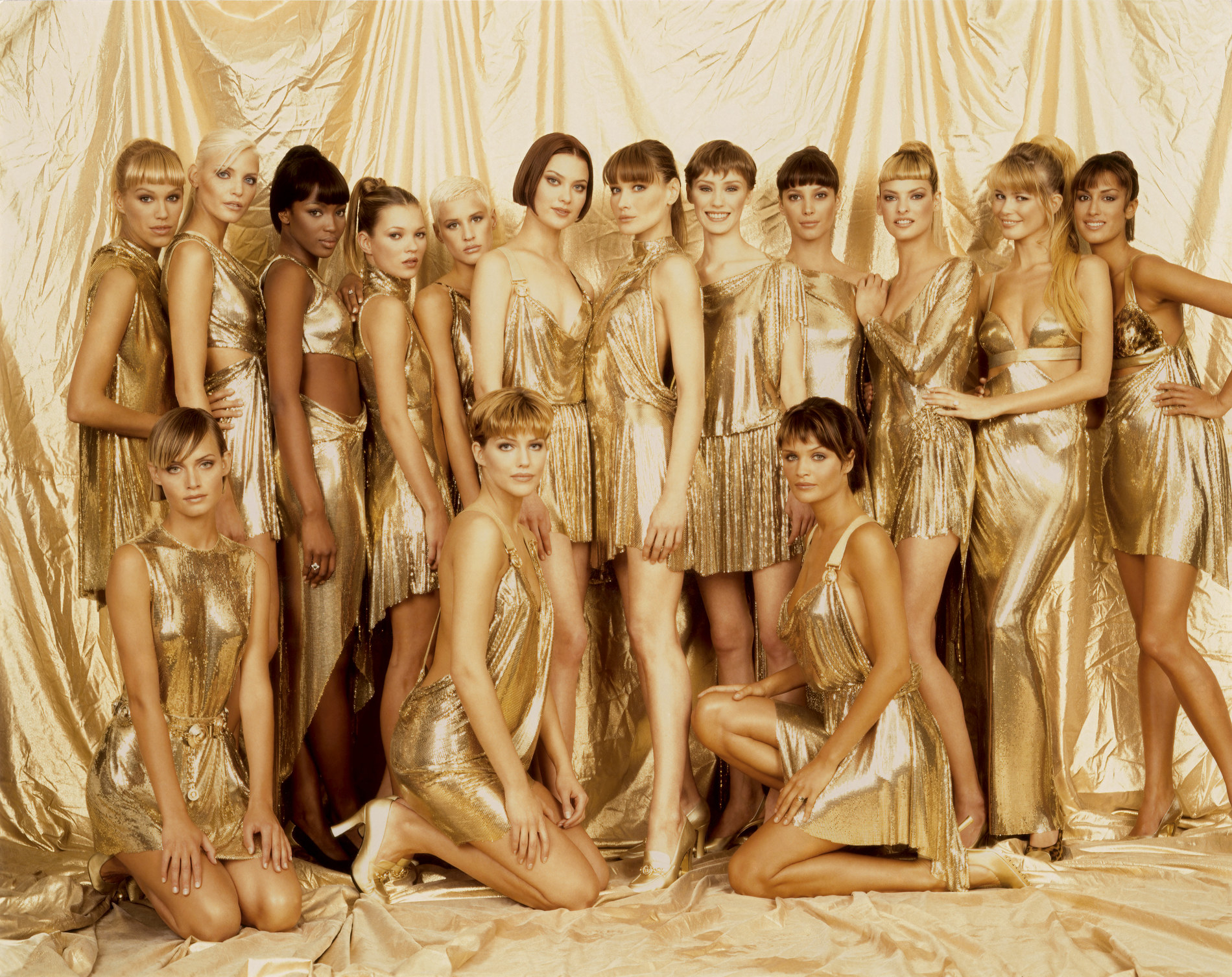 A large group of models in gold outfits on a gold background, looking at the camera