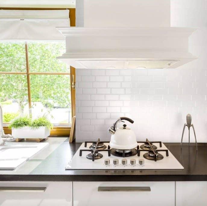 White peel and stick tile backsplash shown in a kitchen.