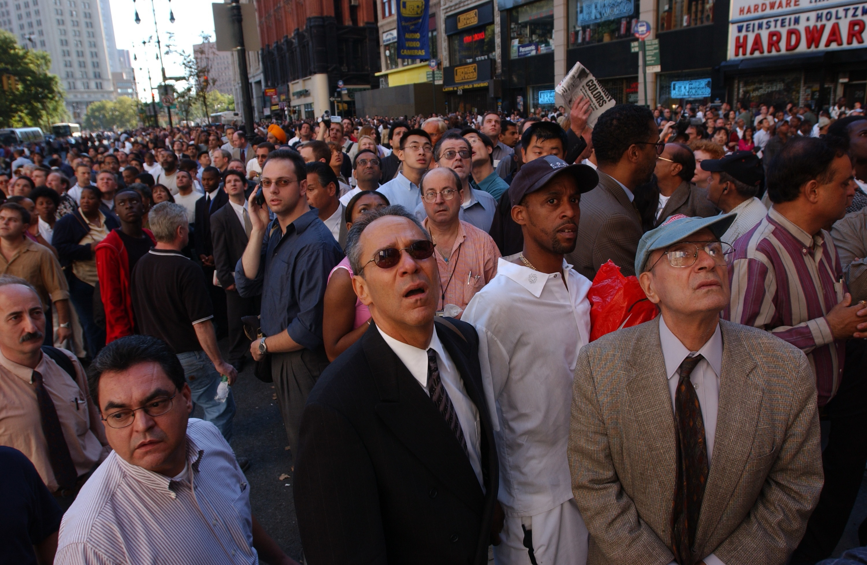 A crowd of people in business clothes looking up