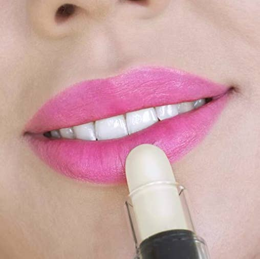 model applying a white lipstick to her lips as it changes to pink when applied