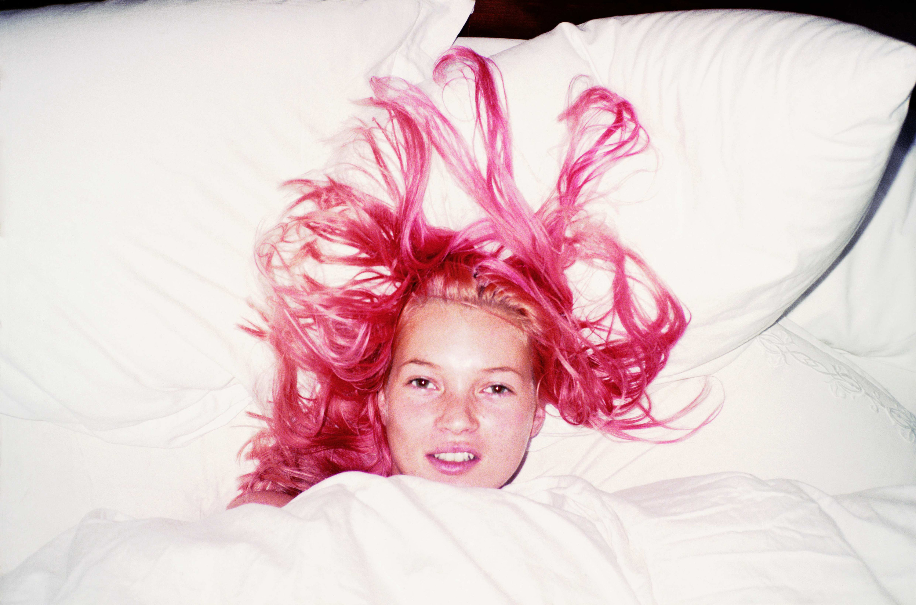 Kate Moss with pink hair wrapped up in blankets in bed