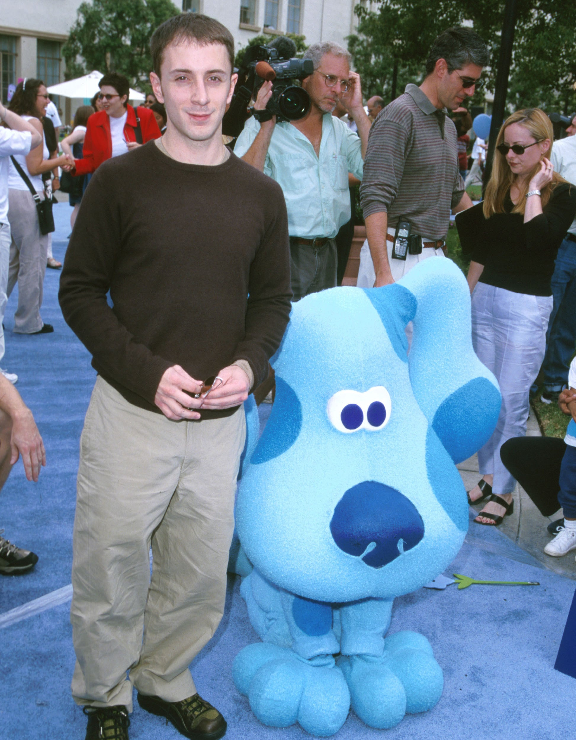 Steve standing on a blue carpet at an event next to a life-size Blue mascot