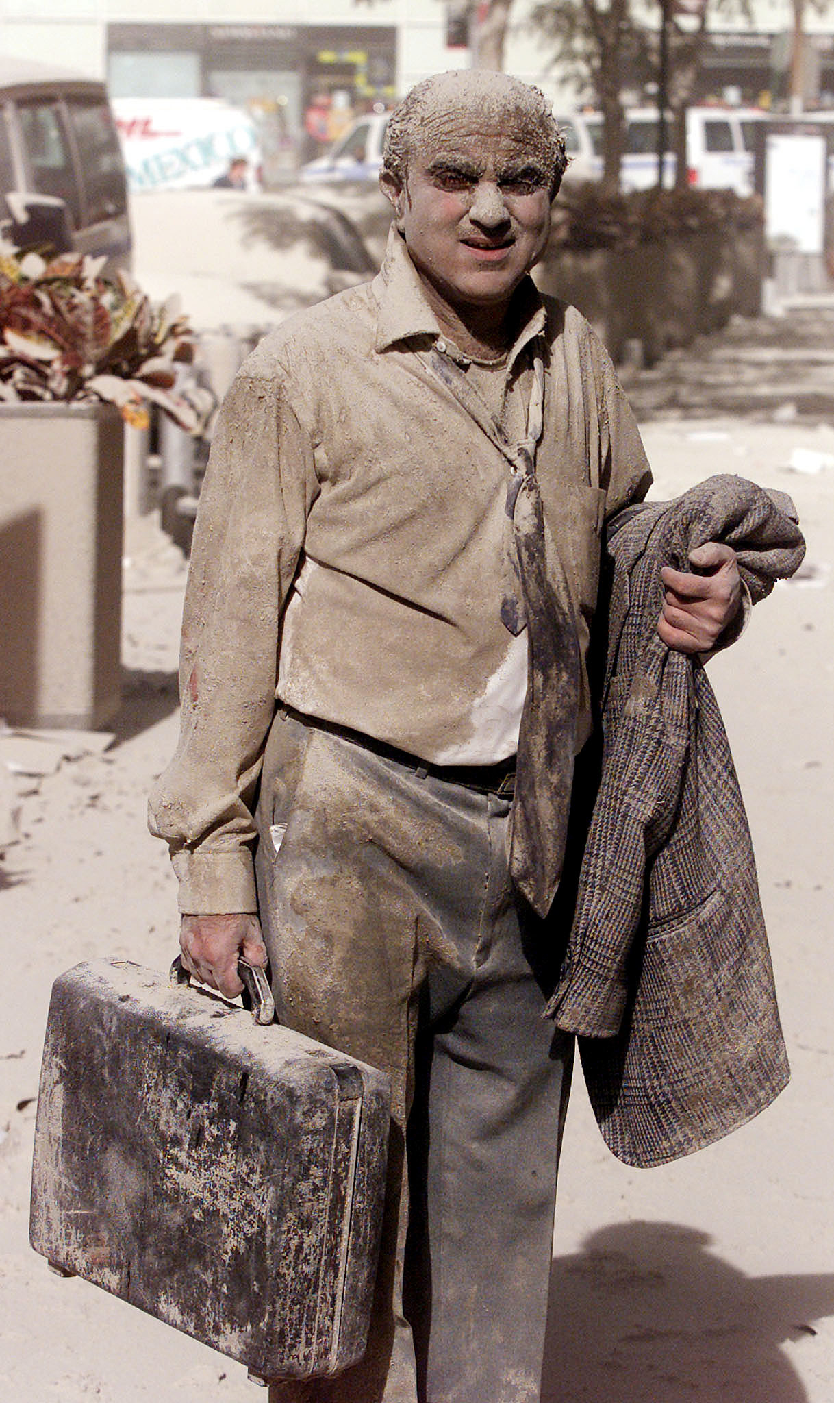 A man holding a briefcase and suitcoat totally covered in dust and ash