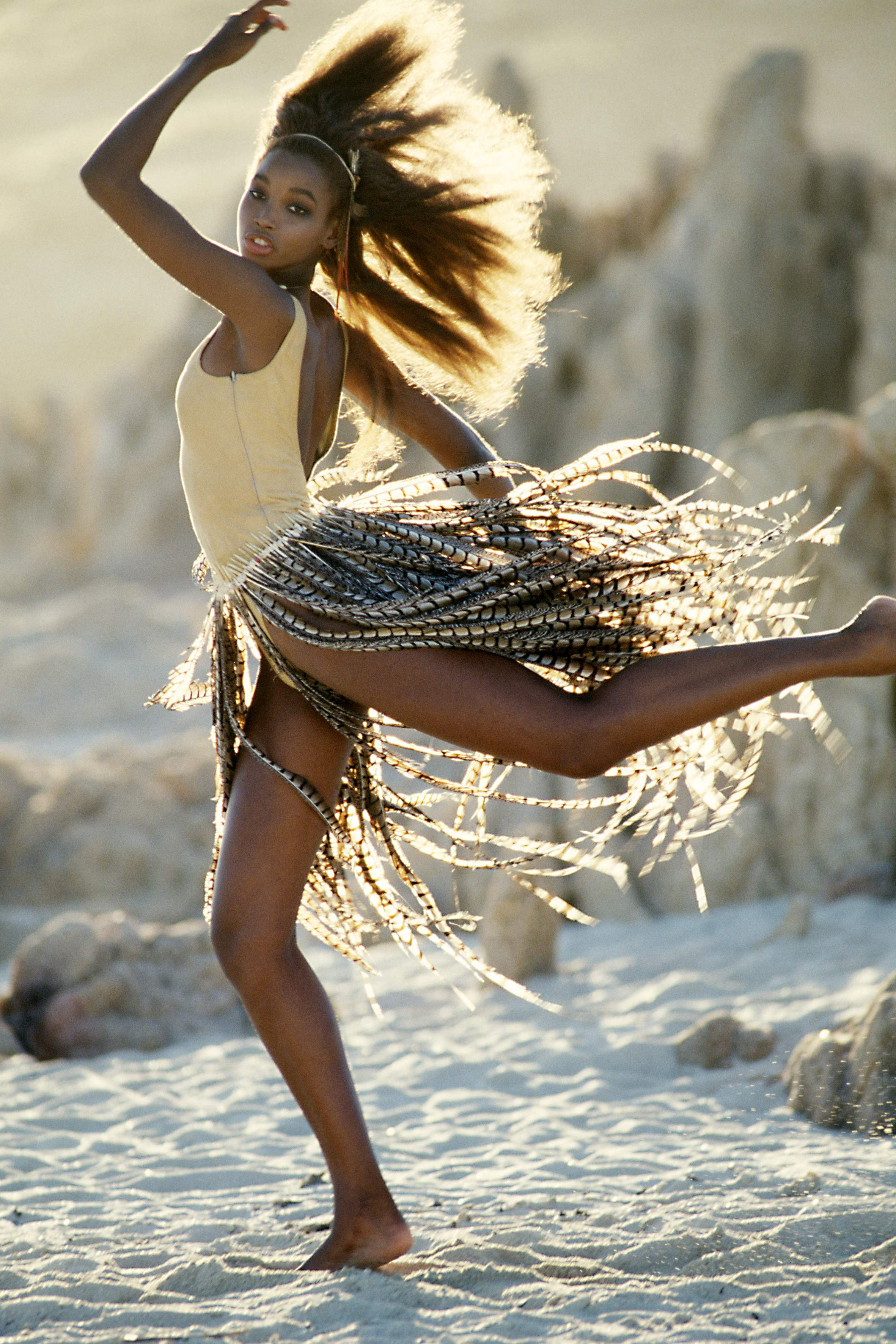 Beverly Peele striking a dance pose on a beach with a feather skirt