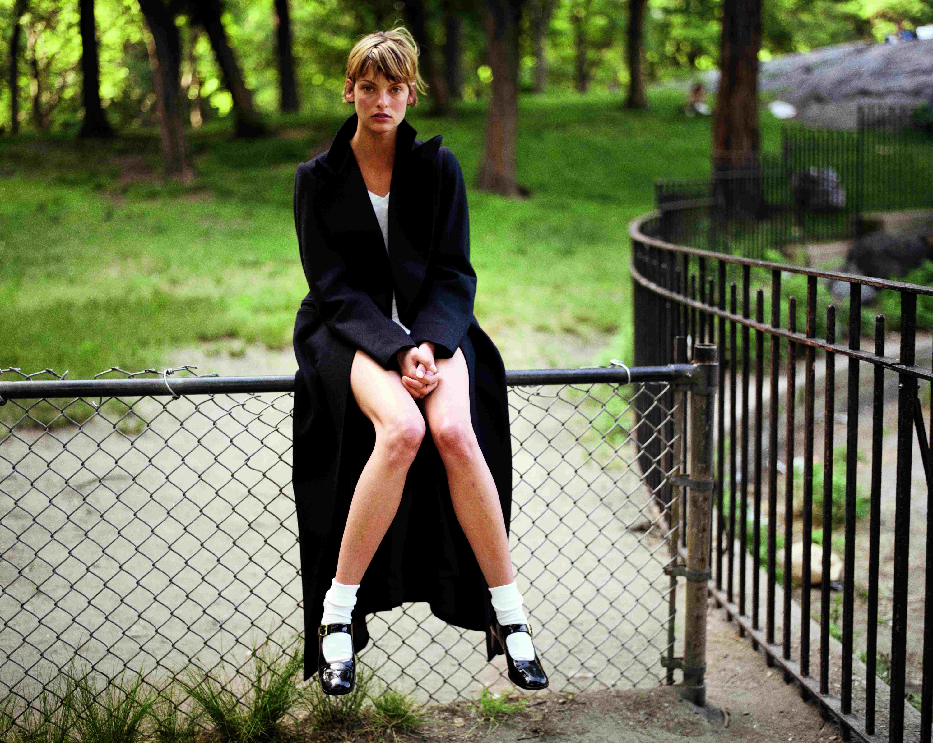 Linda Evangelista sitting on a railing in Central Park with a long wool coat and Mary Janes