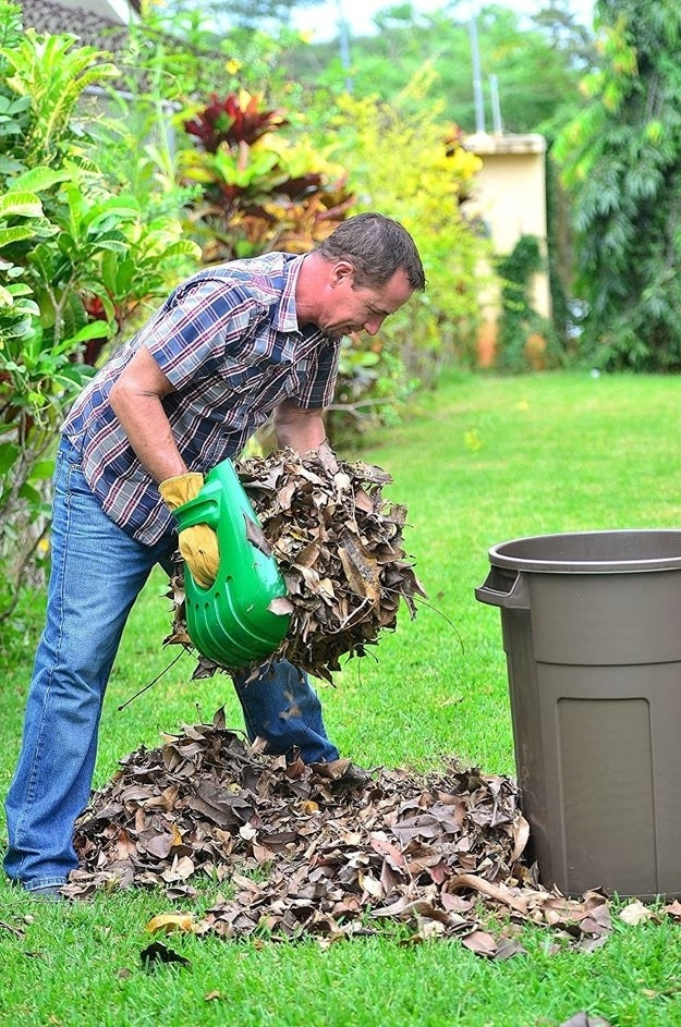 Model holding the scoops and transferring a large handful of leaves into a trash can