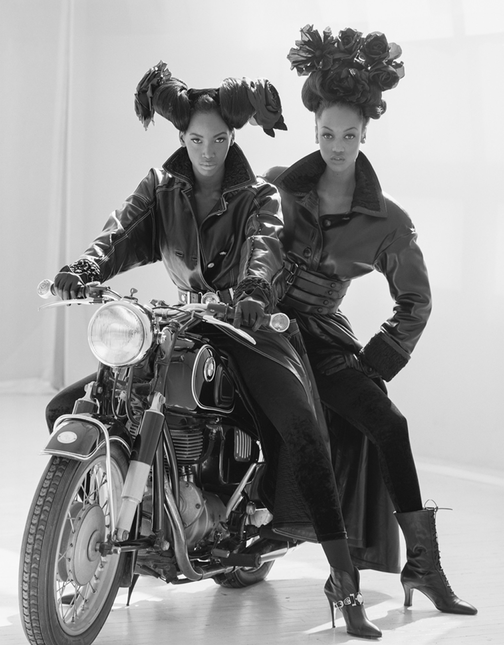Two women in leather on a motorcycle in a studio, looking at the camera