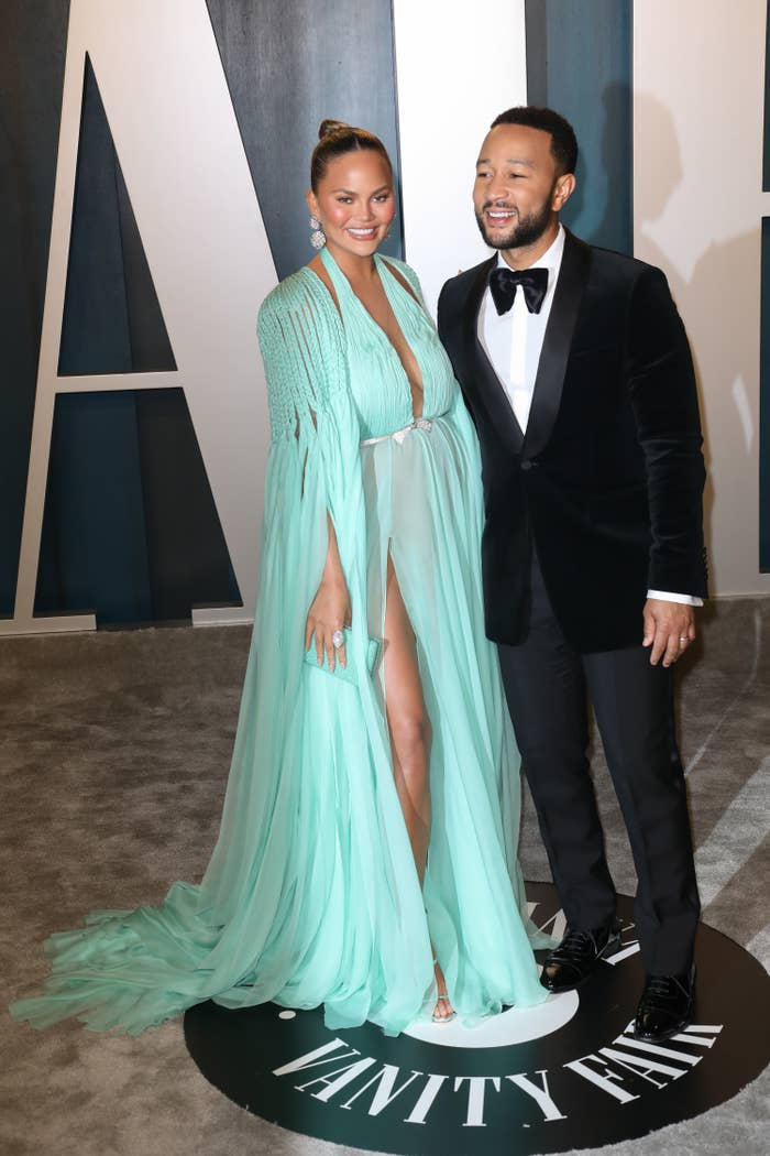 Chrissy, in a long flow-y gown, poses with her husband John Legend at an Oscars after party
