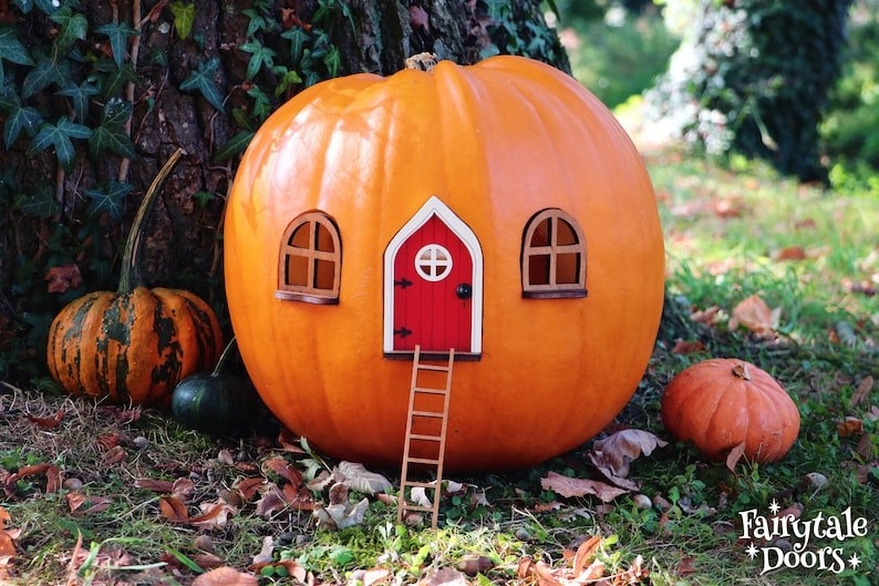 a pumpkin with two windows and a red door on it