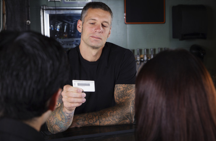 Bartender looking at ID