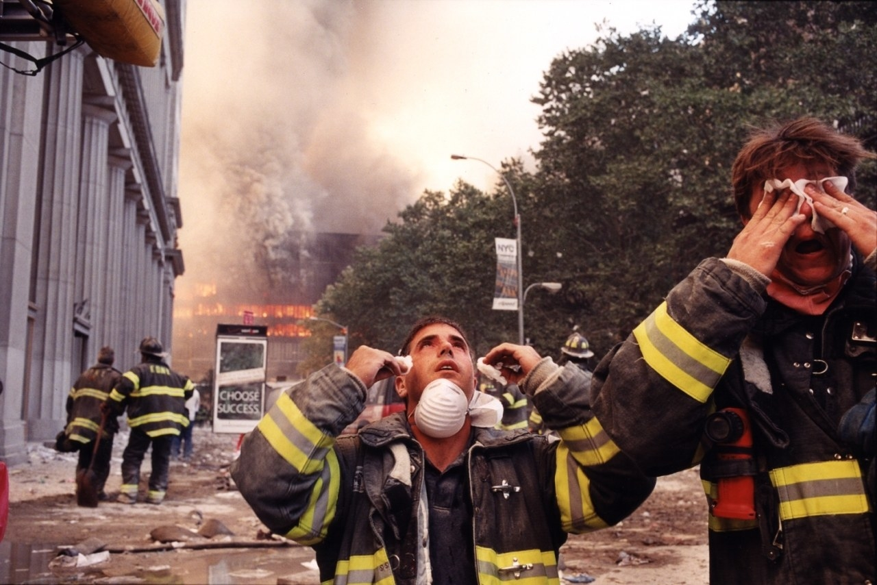 Firefighters wipe their eyes as buildings burn in the background