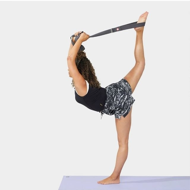 a model using the manduka yoga strap