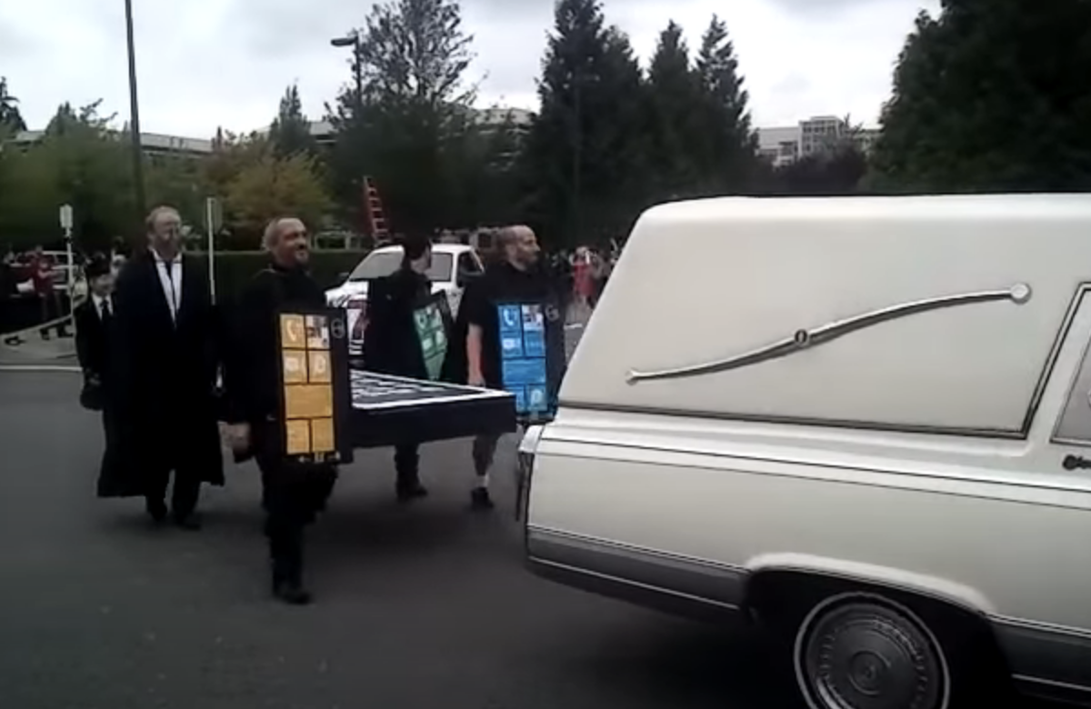 A hearse driving down a street followed by people dressed as Windows phones holding a big cardboard iPhone like a coffin
