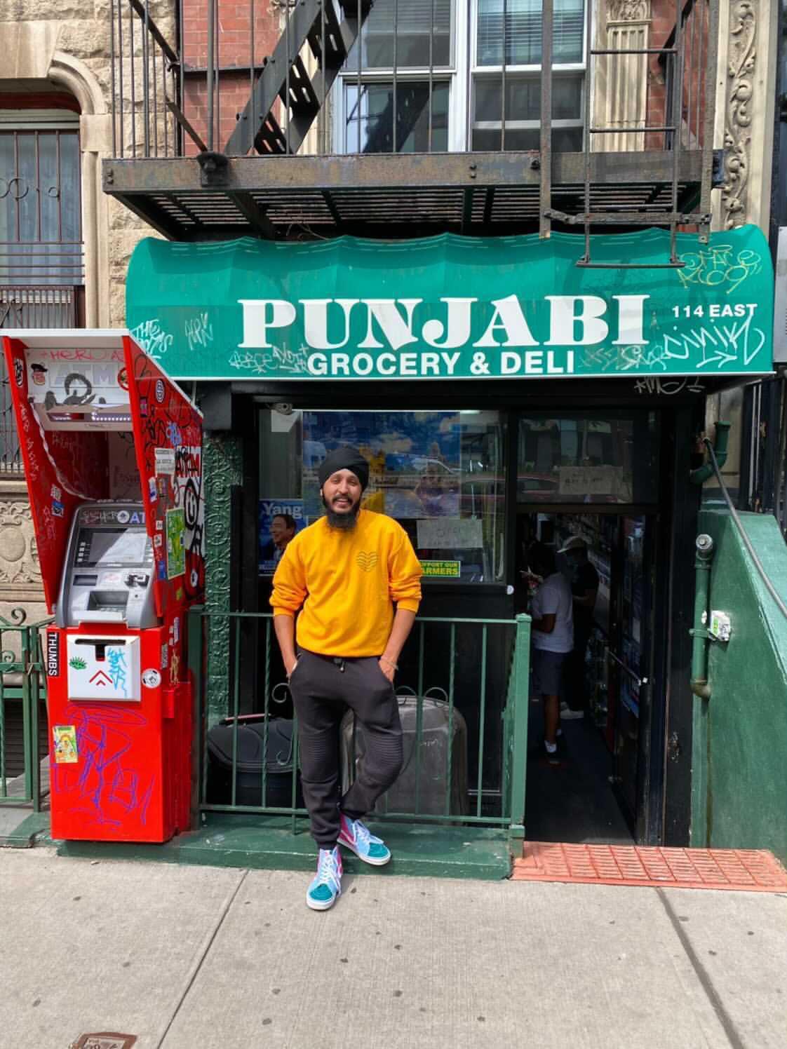 Gurpreet standing in front of the Punjabi Grocery & Deli in New York City
