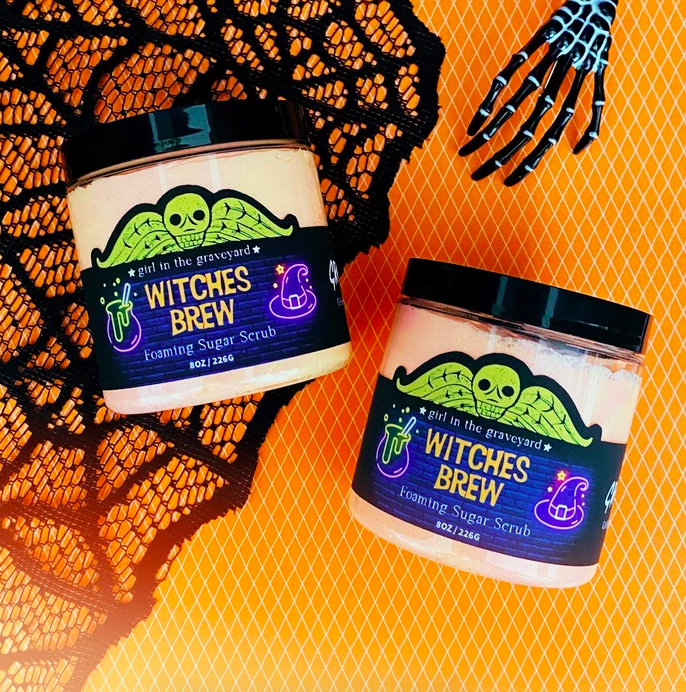 two tubs of the scrub with a green skull on top with wings plus an animated cauldron and witch hat