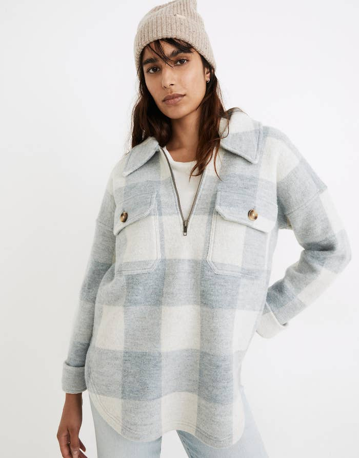 a model in a light blue and white buffalo check half zip top