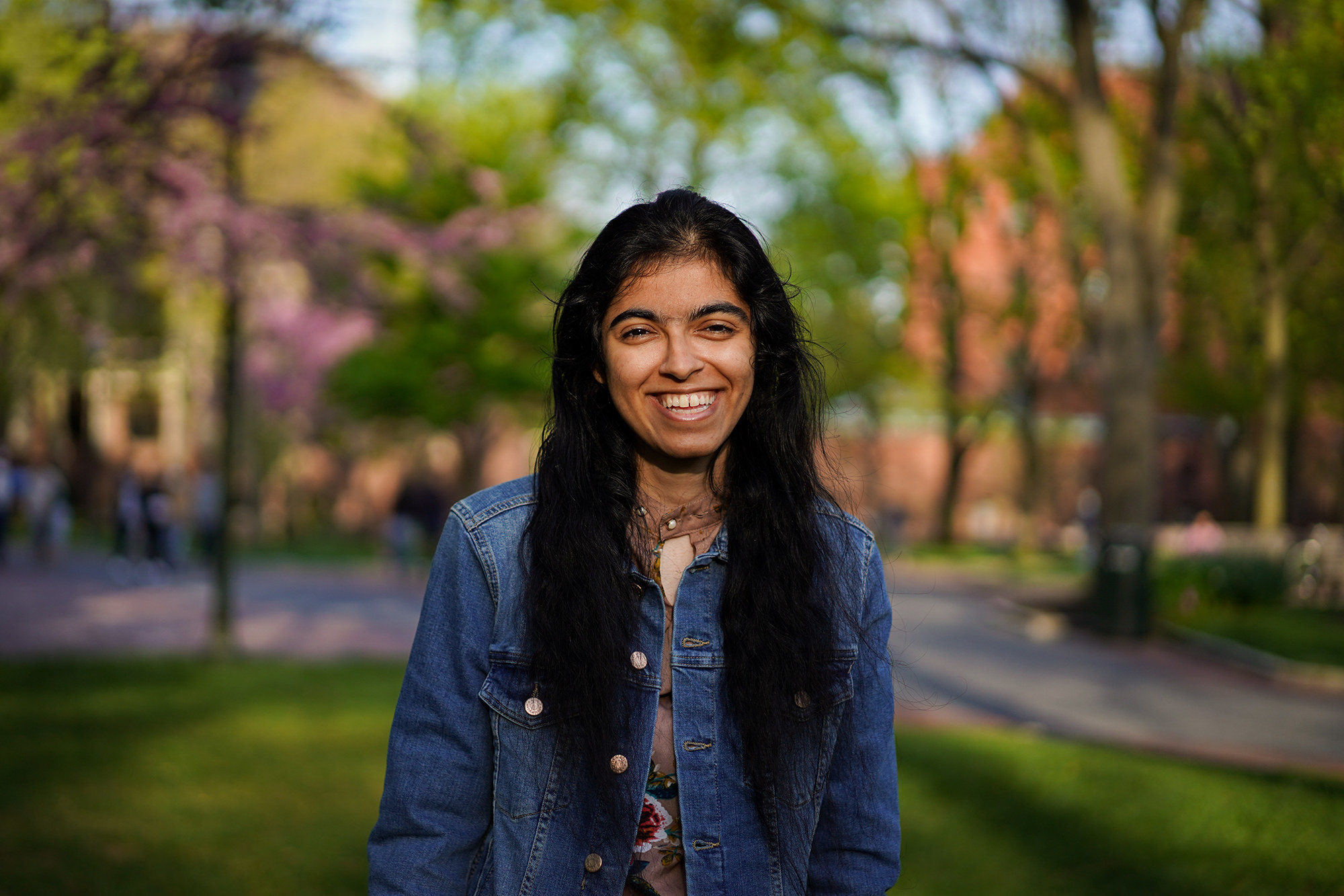 Sukhmani standing in some grass, smiling for the camera while on a campus