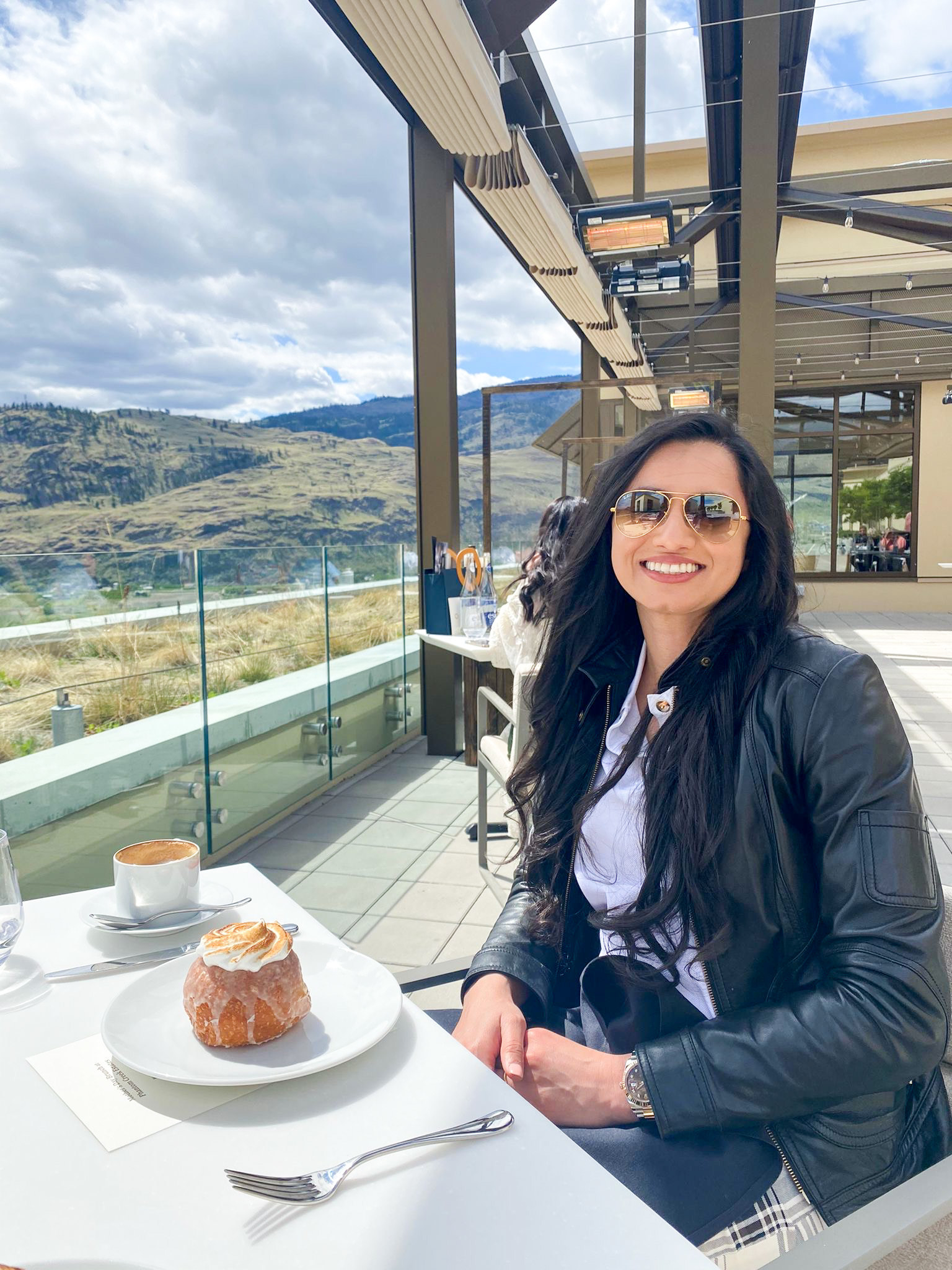 Mandeep sitting at an outdoor table at a restaurant next to a dessert on her table