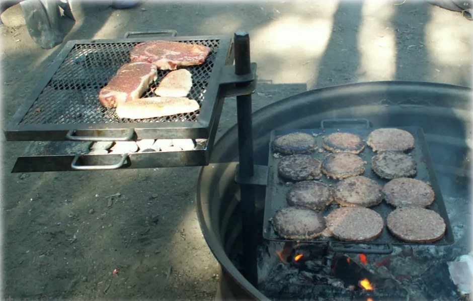 A grill with hamburgers on one side and steak on the other