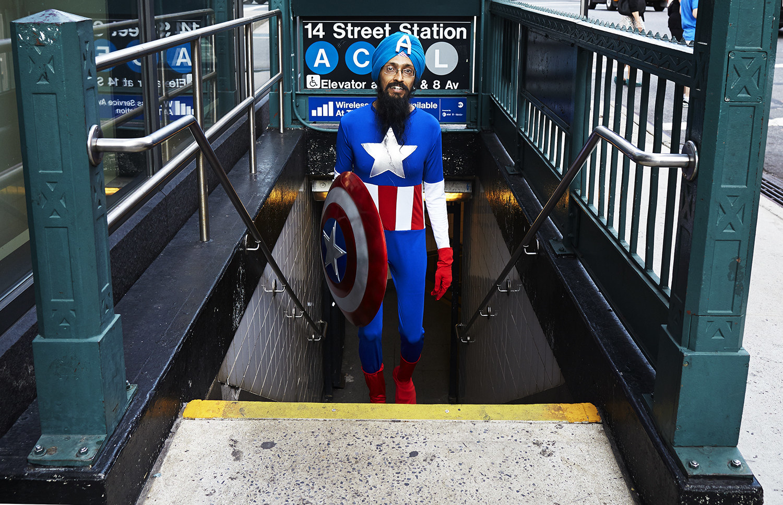 Vishvajit Singh in a Captain America uniform walking out of a subway station