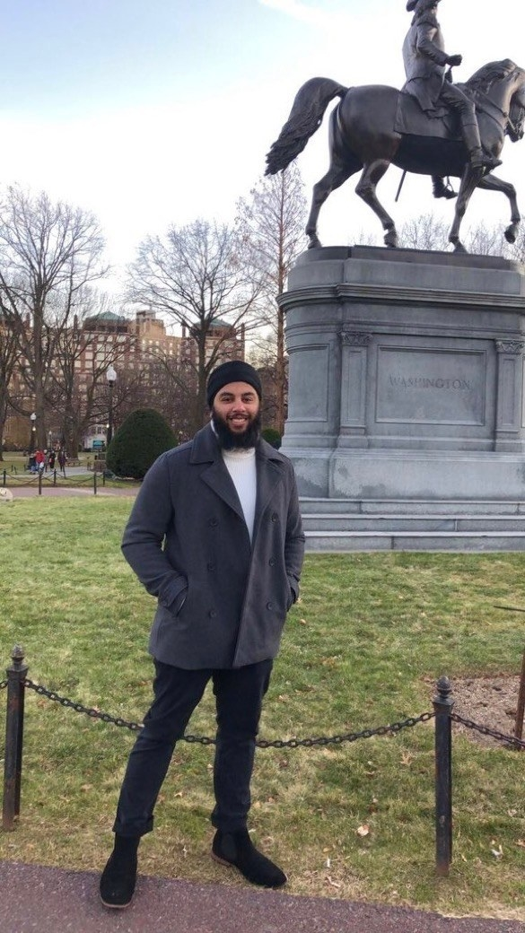 Mohmeet Singh standing in front of a statue of George Washington