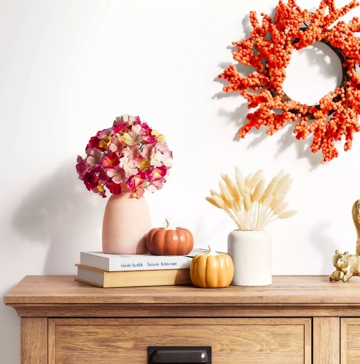 Two of the ceramic pumpkins displayed atop a dresser