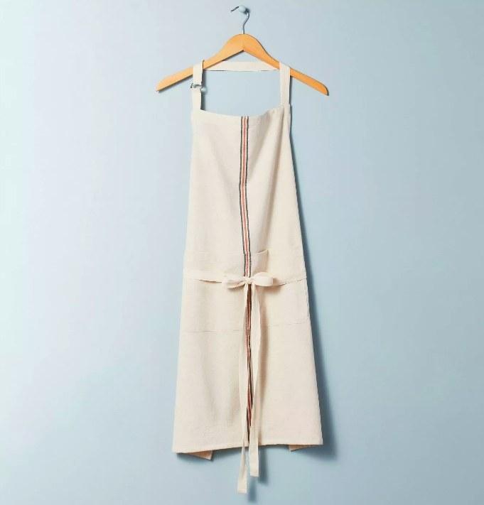 The cream colored apron with a grey and orange center stripe