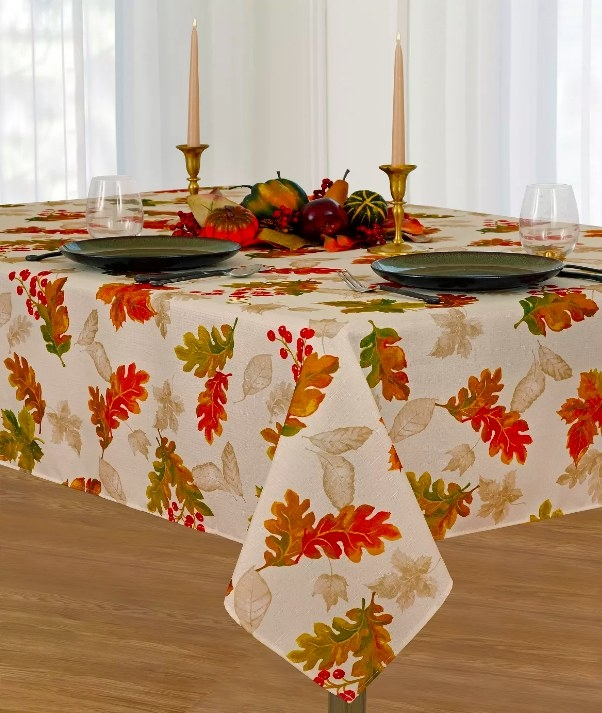 The cream colored tablecloth with orange and red leaves