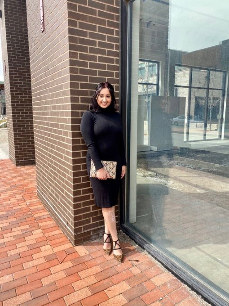 Komal holding a purse and standing in front of a brick wall