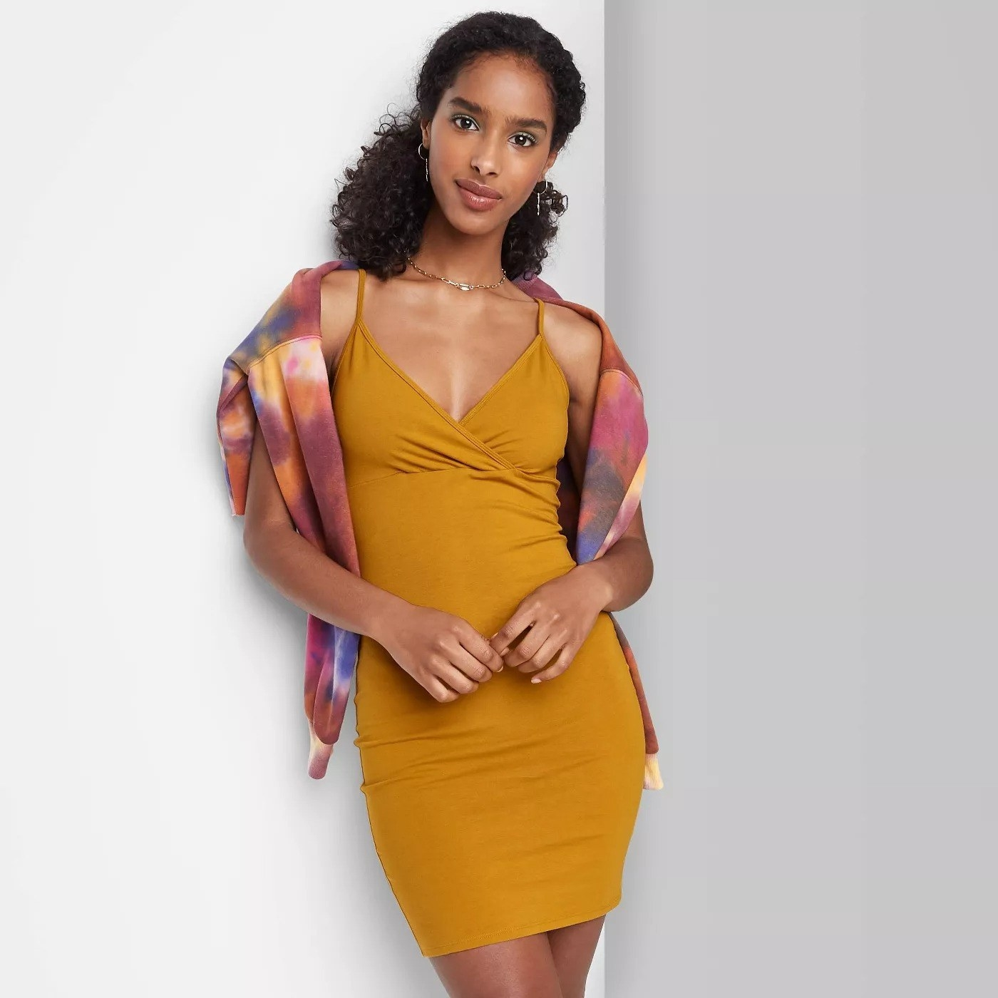 Model wearing yellow dress with thin straps, stops at the knee