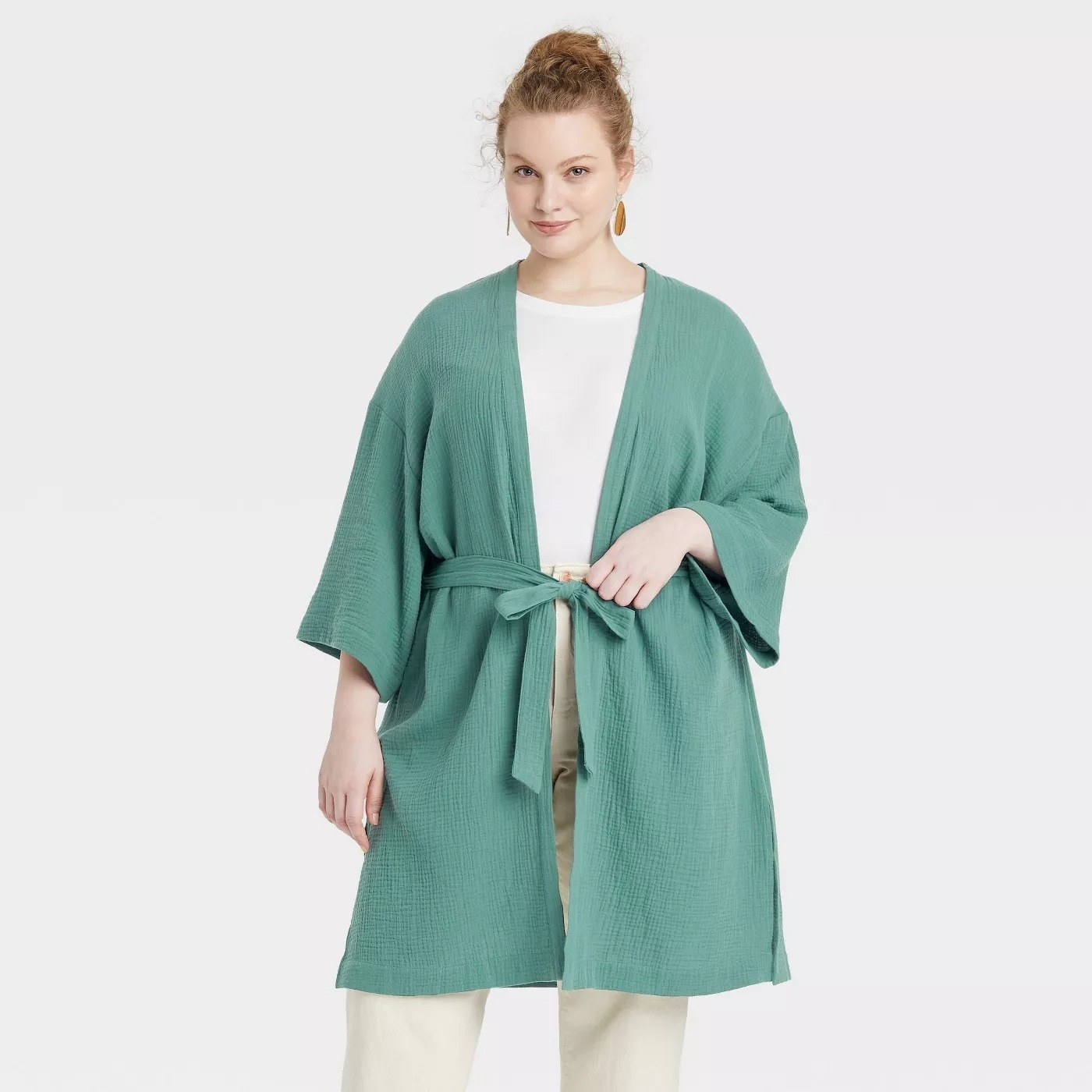 Model wearing long sleeve teal duster, stops above the thigh, tie waist