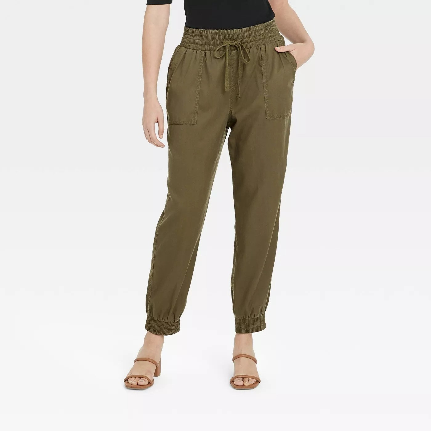 Model wearing green pants with side pockets and tie string detail around waist