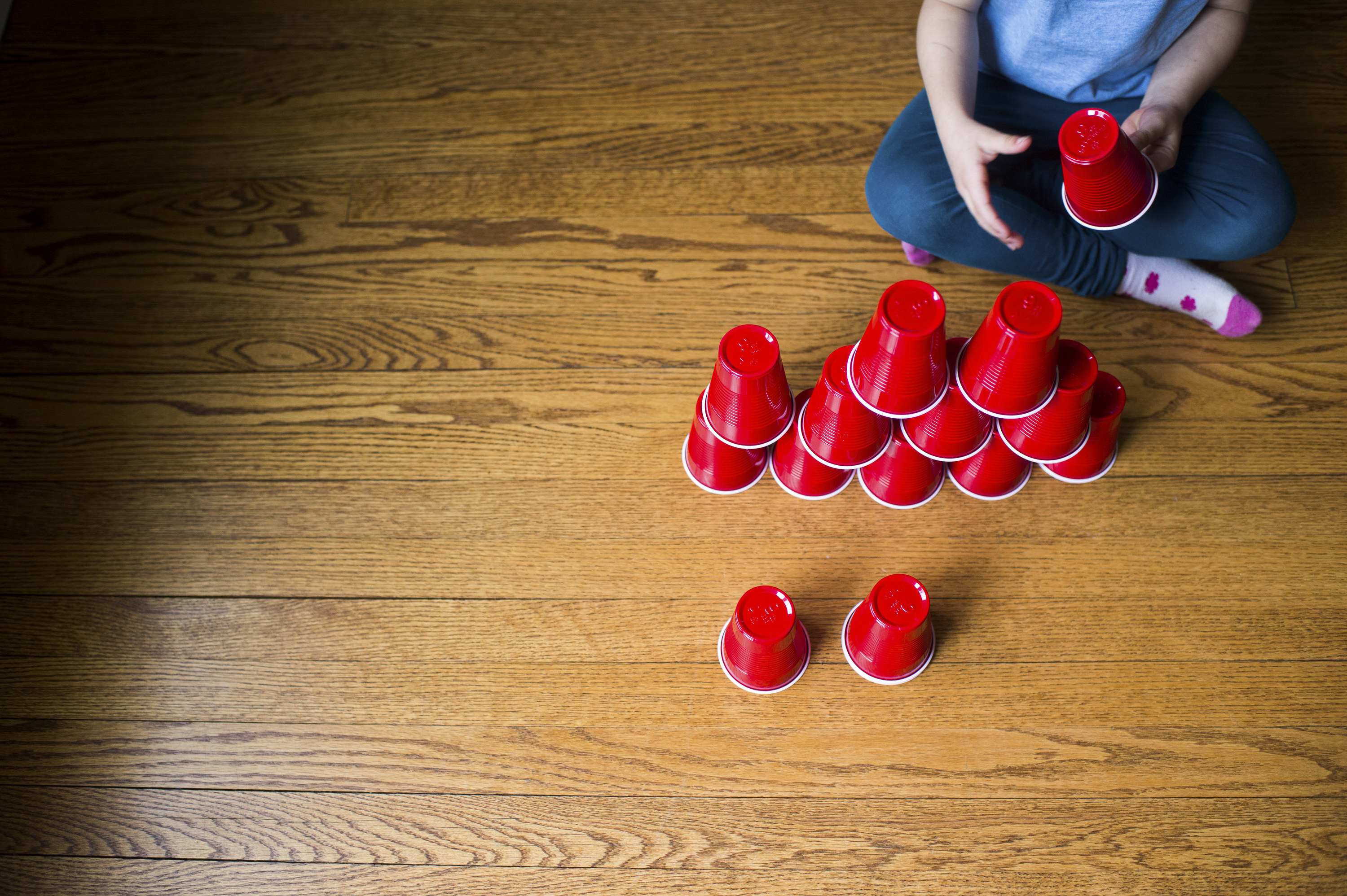 Child stacks plastic cups into a pyramid shape on a wooden floor.