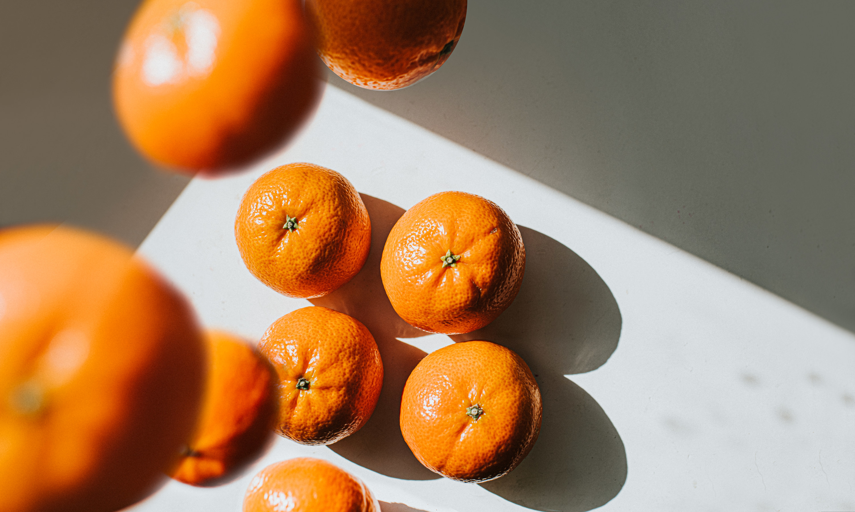 Oranges falling onto a white surface.