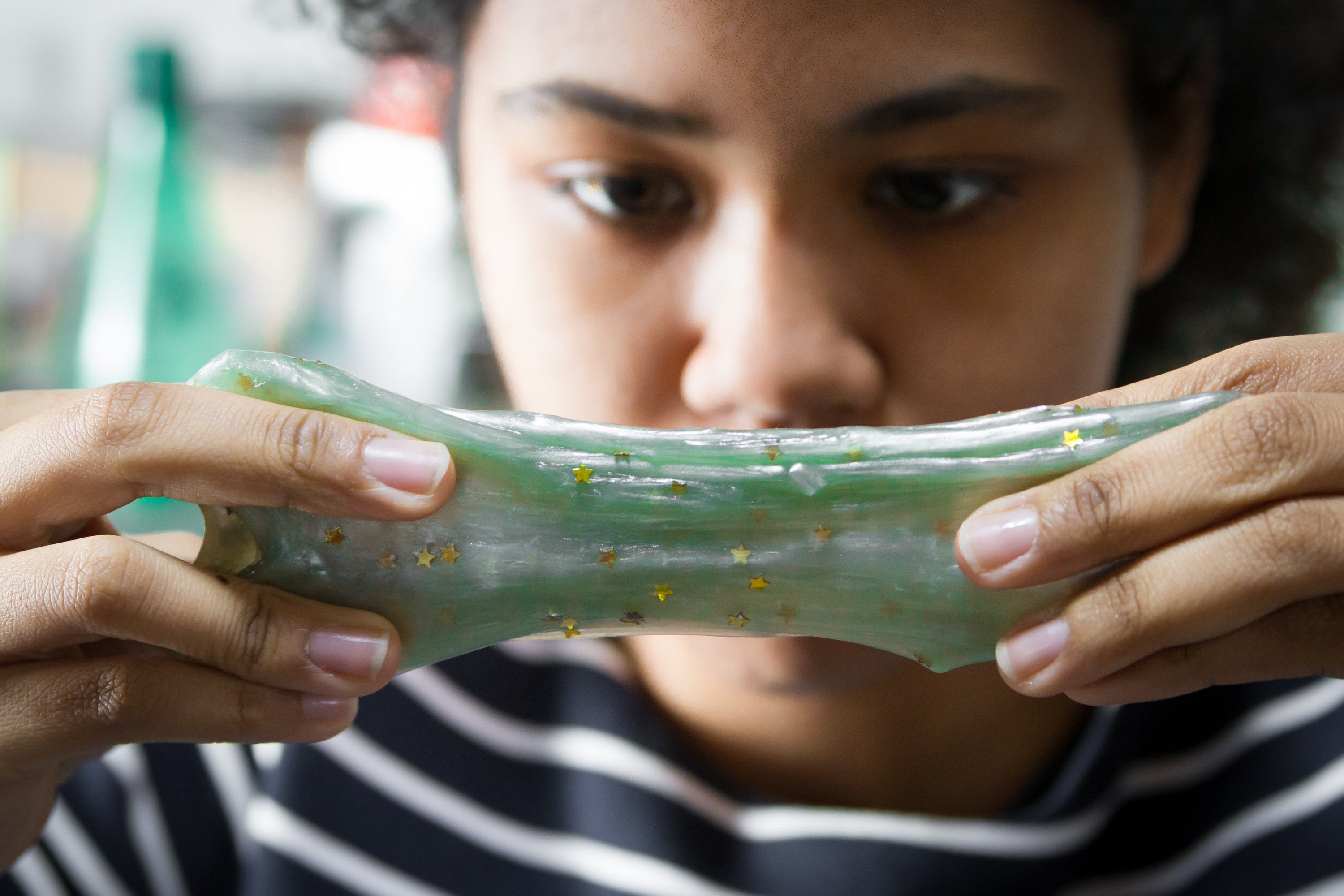 A girl looks intently at a glittery and stretched piece of slime she is stretching between her hands.