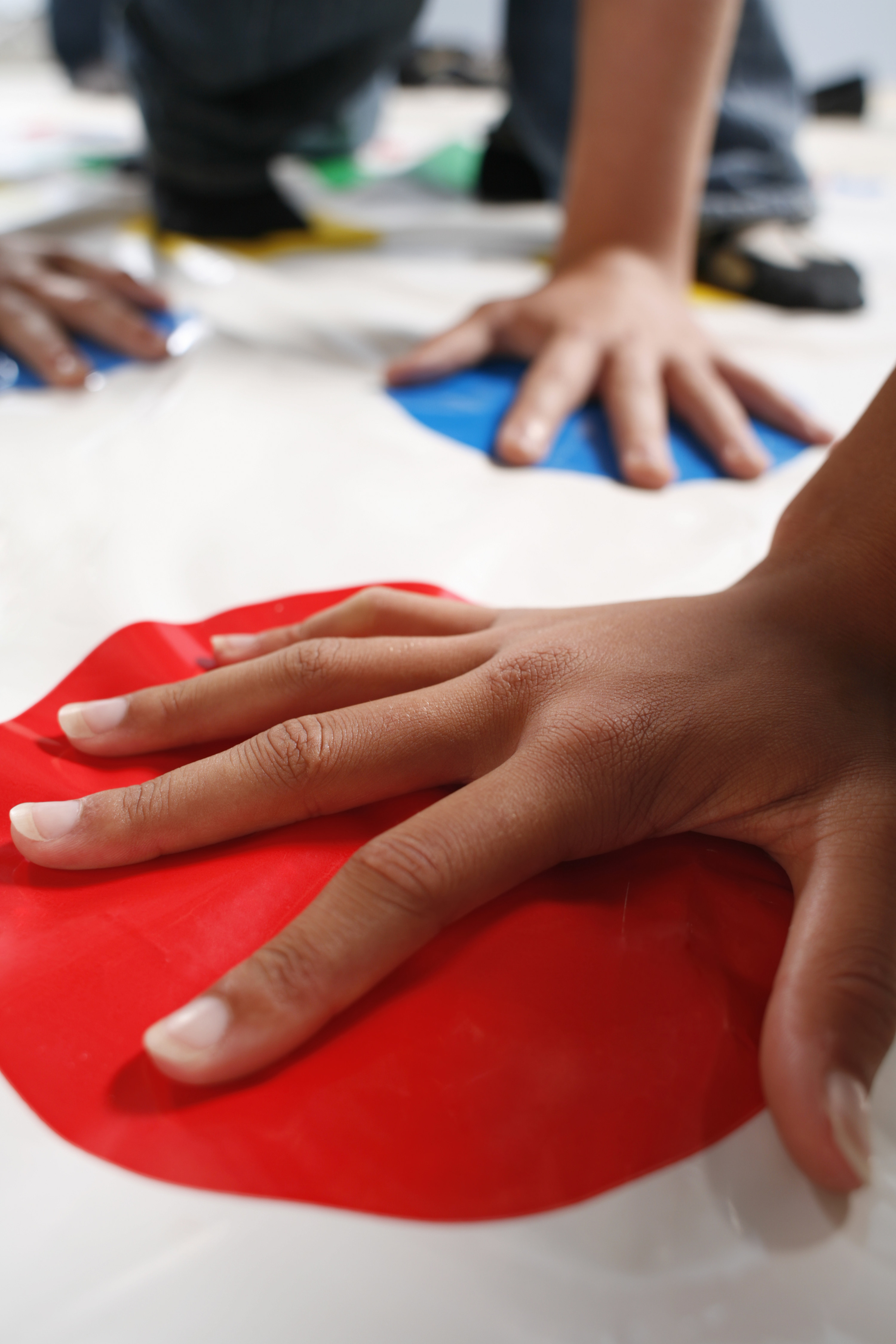 Hands being placed on various circles of color on a Twister game mat.